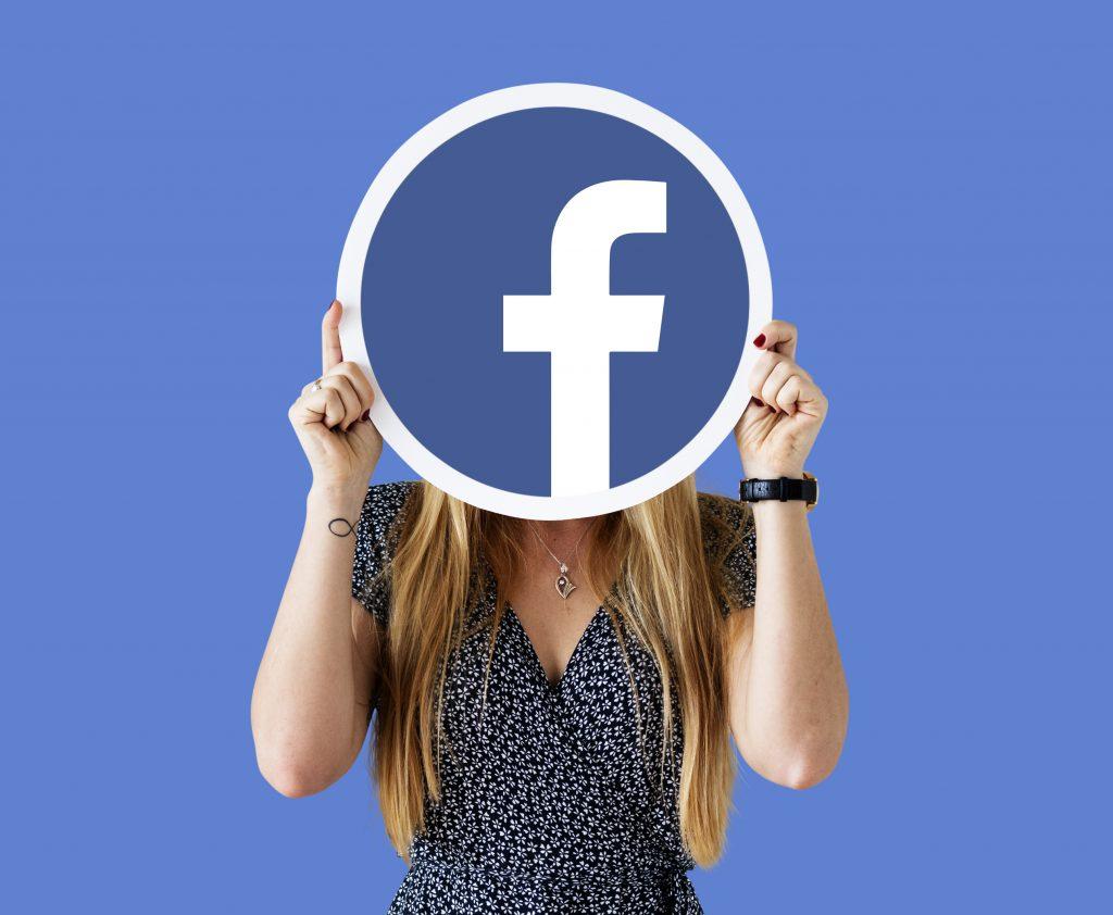 Lány, kezében egy facebook táblával, Ő tudja a tökéletes Facebook poszt titkát.
